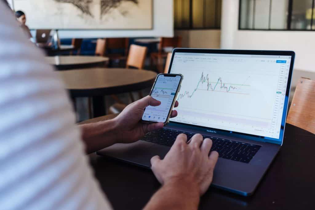 Mann sitzt mit Smartphone am Computer und schaut sich die Displays an